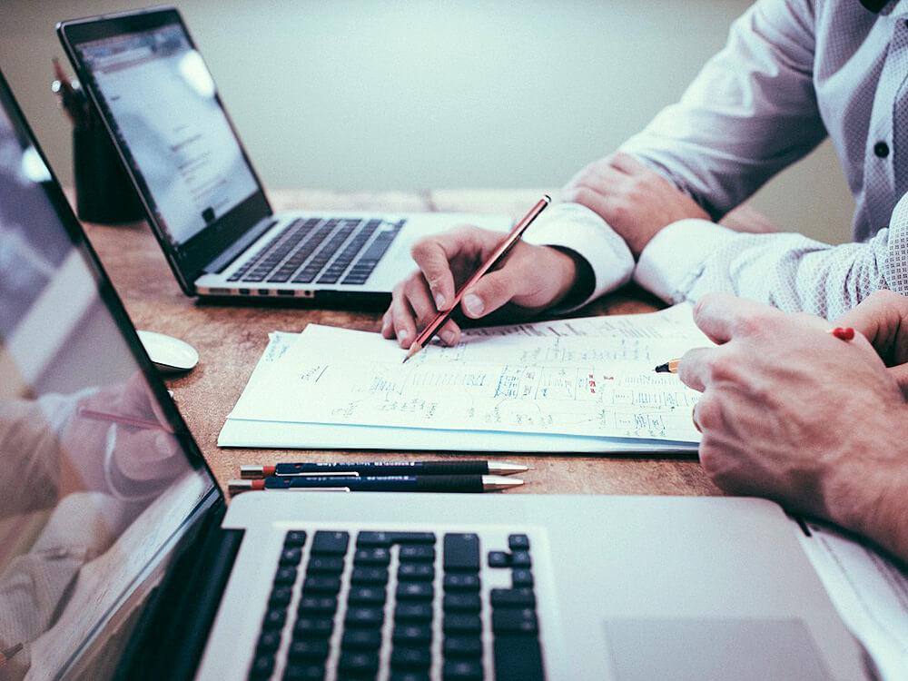 Fotografía de dous ordenadores portátiles e dúas persoas a ver uns documentos